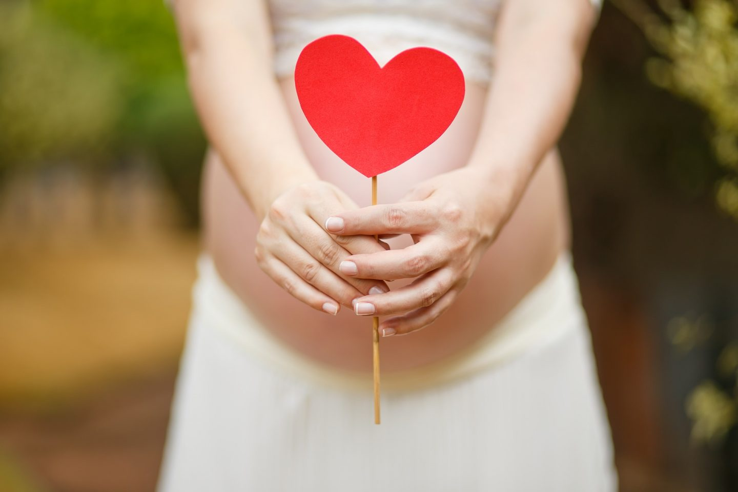 pregnant woman holding heart