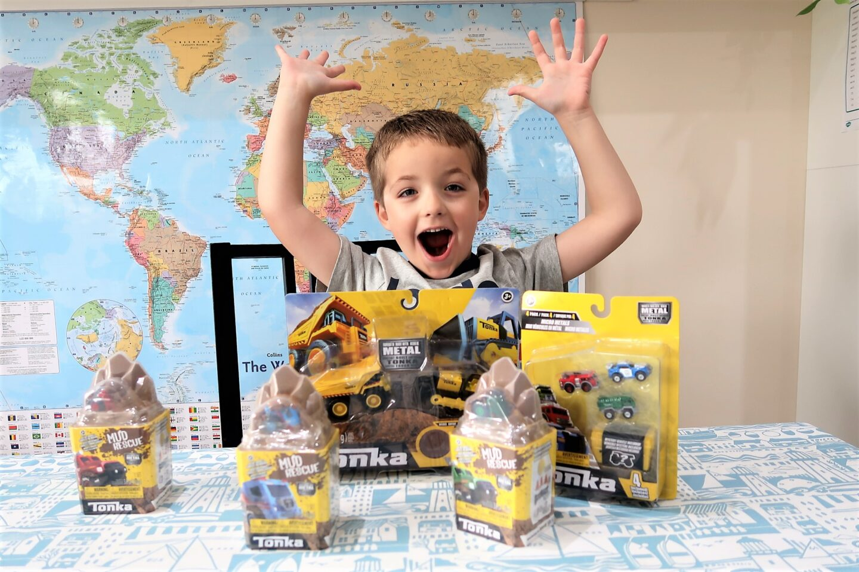 boy happy with tonka toys